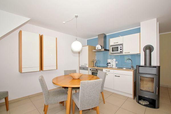 Küche mit Essbereich und Kamin in der Wohnung 06 im Haus 28 im Strandresort Rex Rugia