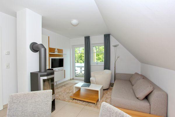 Wohnzimmer mit Kamin in der Ferienwohnung 08 im Haus 28 im Strandresort Rex Rugia