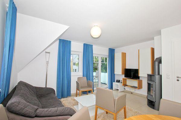 Wohnbereich mit Kamin in der Ferienwohnung 07 im Haus 29 im Strandresort Rex Rugia